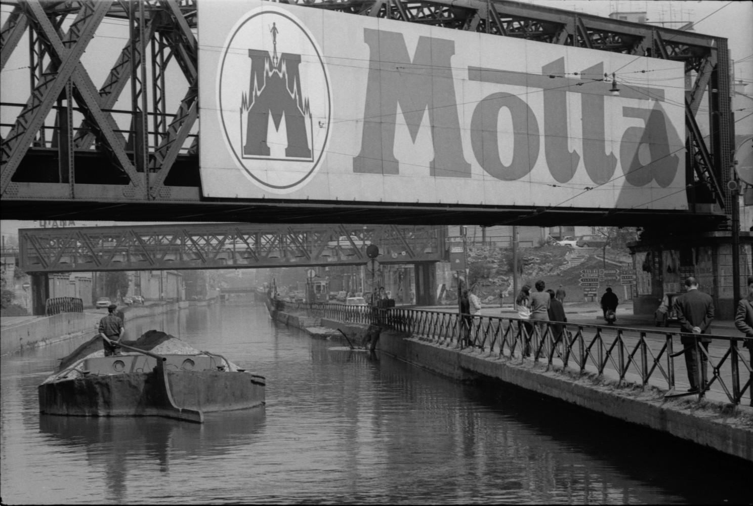 Toni Nicolini, Uomo trasporta della ghiaia sul barcùn, la tradizionale chiatta milanese, lungo il Naviglio Grande a Milano, Milano, 1970