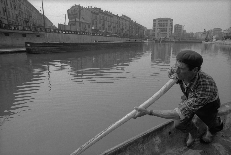 Toni Nicolini, Uomo trasporta della ghiaia sul barcùn, la tradizionale chiatta milanese, nella Darsena di Milano, Milano, 1970