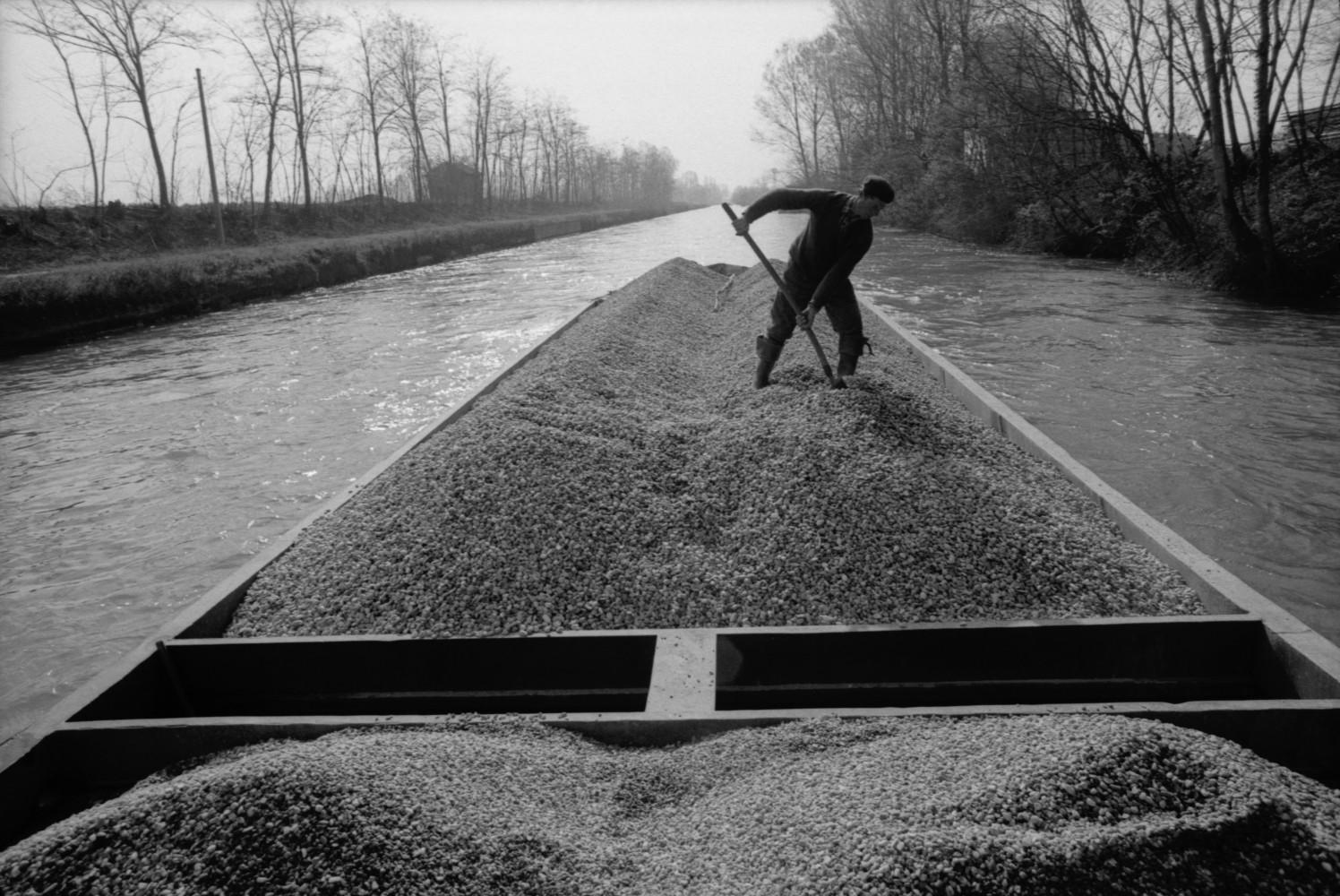 Toni Nicolini, Uomo trasporta della ghiaia sul barcùn, la tradizionale chiatta milanese, lungo il Naviglio Grande, Milano, 1970