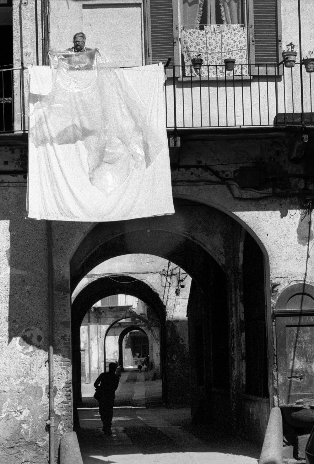 Toni Nicolini. Cortili di via Col di Lana 10. Donna stende il bucato Milano, 1978